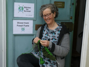 Woman knitting with a Stitches For Survival sign on the door behind