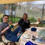 Two young women knitting in the garden