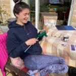 Young woman knitting in the garden
