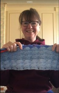 Woman holding a piece of blue crochet with wave shapes